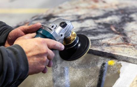Natursteinmechaniker welcher gerade die Kanten eine Rohplatte bearbeitet