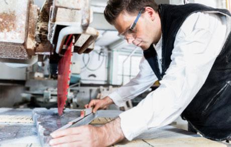 Naturwerksteinmechaniker in der Produktion welcher gerade Maß einer Platte nimmt