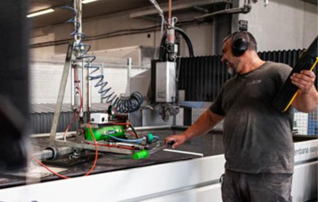 Naturwerksteinmechaniker in der Produktion welcher gerade an der Fräsmaschine arbeitet