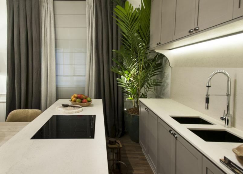 Foto einer hellen Küche mit heller Keramik Arbeitsplatte Dekton Danae