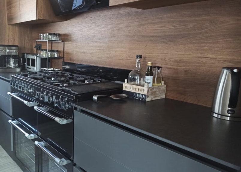 Foto einer Küchenzeile an der Wand aus dem dunklen Material Dekton Eter