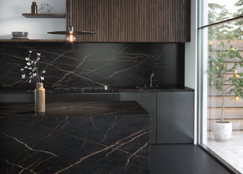 Spülenzeile und Kücheninsel aus dunklem Material mit orange-bräunlichen Adern Dekton Laurent
