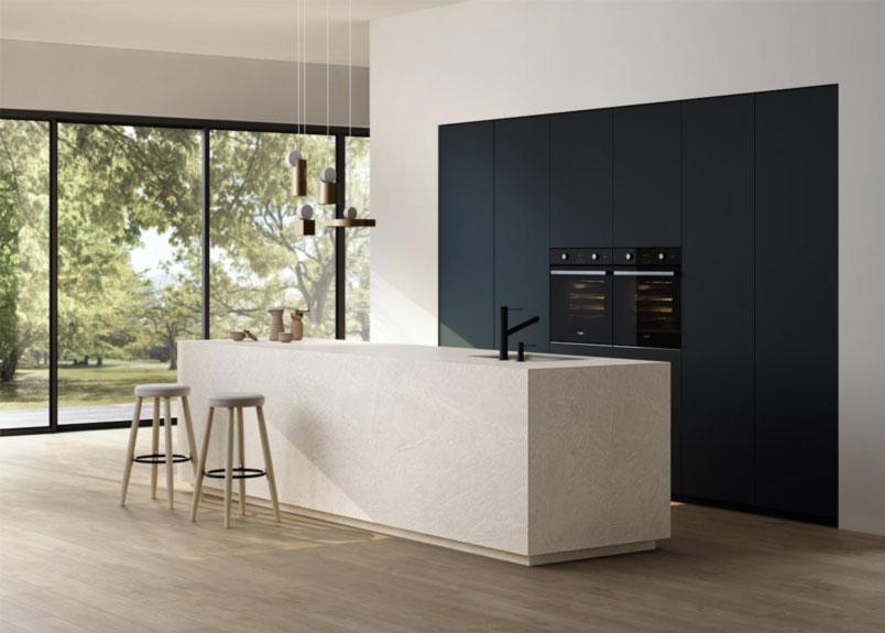 Foto einer hellen Küche in einem leeren Raum die komplett aus Keramik Dekton Liquid Shell angefertigt ist