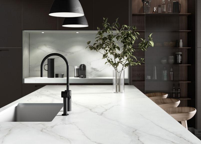 Helle Kücheninsel Barhocker und Spülenzeile an der Wandseite aus dem Material Dekton REM