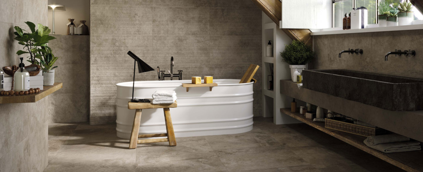 Wellness Badezimmer aus beige-grauen Fliesen mit Badewanne und großem Waschtisch