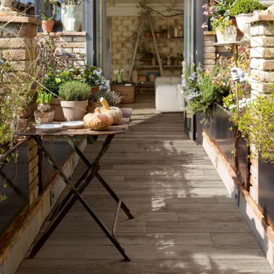 gemütlicher rustikaler Balkon mit Holzfliesen aus Keramik und mediterraner Bepflanzung und Kräutern