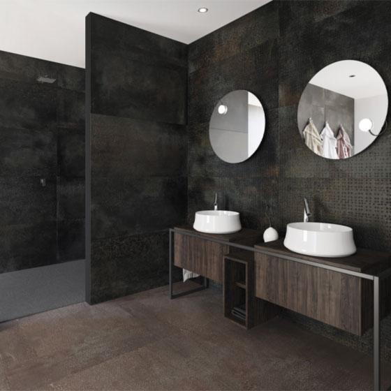 Badezimmer mit Wandverkleidung aus Fliesen in anthrazit-brauner Metalloptik, dunklem Wachtisch und zwei weißen Keramikwaschbecken