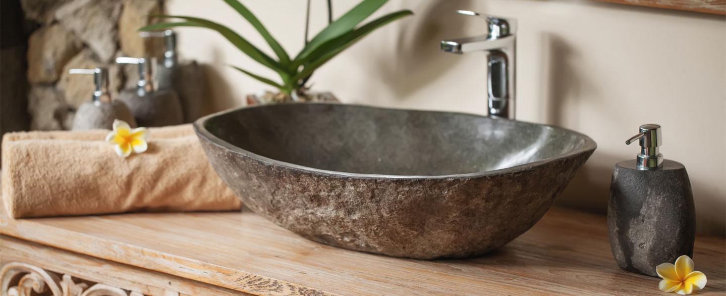 Flusssteinwaschbecken auf einem Holzwaschtisch mit Seifenspender aus Stein und gerollten Handtüchern