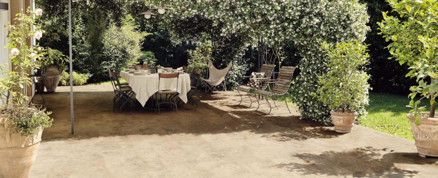 gemütlich rustikale Terrasse mit Laube, mediterraner Bepflanzung und gedecktem Holztisch