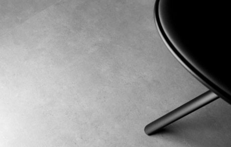 Detailansicht einer Fliese für den Innenbereich in Betonoptik worauf ein schwarzen Stuhl drauf ist