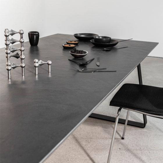 angeschnittene Ansicht eines Esstisches mit grauer Keramikplatte auf dem schwarzes Geschirr und silberne Kerzenleuchter stehen