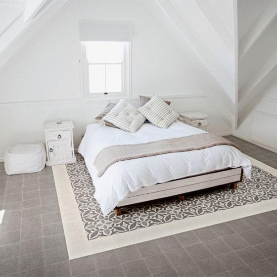 großes Bett mit weißem Bettzeug und gemütlichen Kissen steht auf ornamentalen Zementfliesen im Vintage-Stil