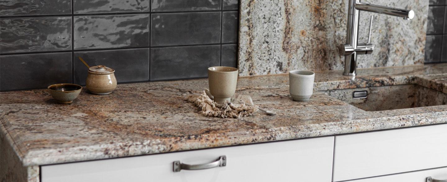 Küchenarbeitsplatte Sage Brush mit Spüle aus dem gleichen Material und mit grauen Majolikafliesen gefliester Rückwand