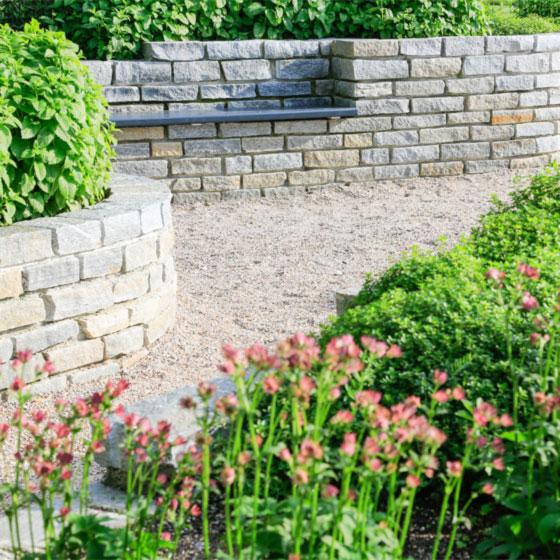 kleine Natursteinmauer mit eingelassener Bank, Bepflanzung und Kiesweg