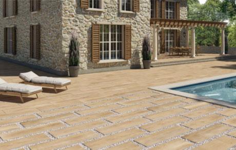 Foto einer Terrasse mit einem Boden aus Wood Honey 01 und einem Haus im Hintergrund