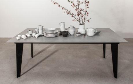 Grauer Esstisch aus Keramik Puristic Grey mit schwarzem Stahlgestell und Geschirr darauf