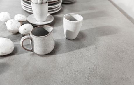 Detailansicht eines grauen Esstisches aus Keramik mit weißem Geschirr darauf