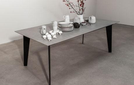 Grauer Esstisch aus Keramik mit schwarzem Stahlgestell und Geschirr darauf