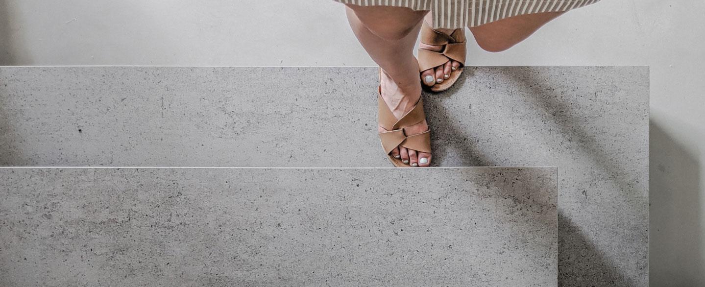 Bild in in Vogelperspektive von zwei Füßen in Sandalen, die Treppenstufen hinaufgehen
