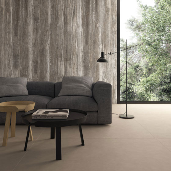 moderne graue Couch, zwei Couchtische und eine Stehlampe vor einer Wand mit Keramikverkleidung in Steinoptik