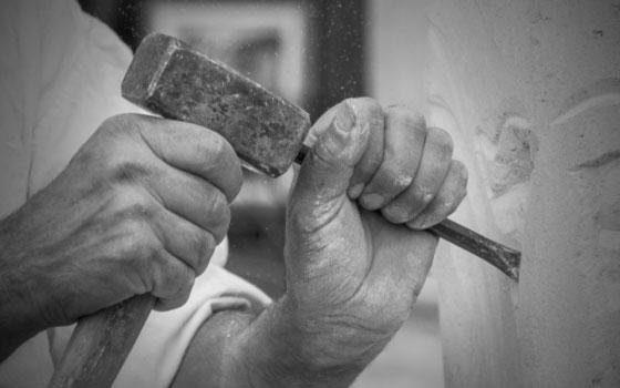 Nahaufnahme zweier Hände, die mit Hammer und Meissel einen Stein bearbeiten