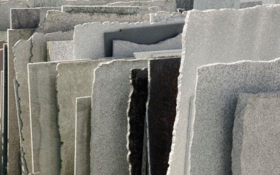 Natursteinrohplatten stehen aufgereiht im Schaulager bei Dinger Stone