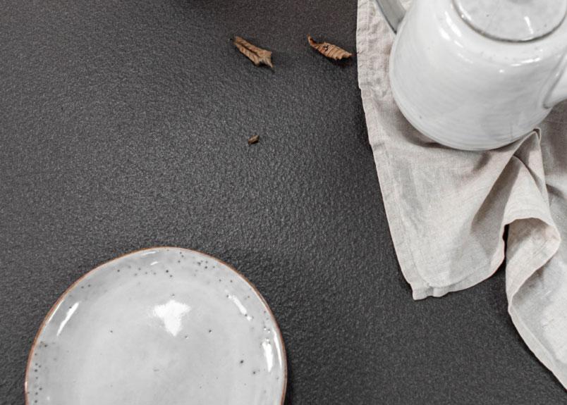 weißgraues Keramikgeschirr auf anthrazitfarbener Keramik Tischpaltte Lapitec Nero Anthracite