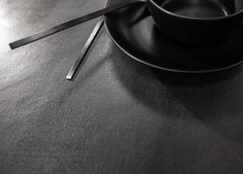 Nahaufnahme schwarzes Keramikgeschirr und schwarzes Besteck auf schwarzer Keramik Arbeitsplatte pureto Lava Night