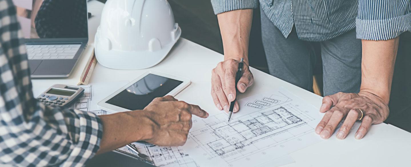 Nahaufnahme eines Bauplans mit zeigender Hand