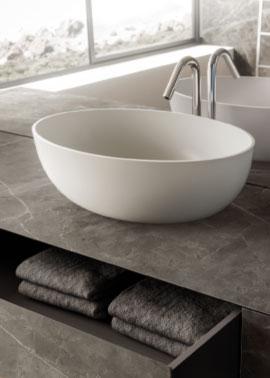 weißes ovales Keramik Aufsatzwaschbecken auf Waschtischschrank aus Keramik in grauer Marmoroptik