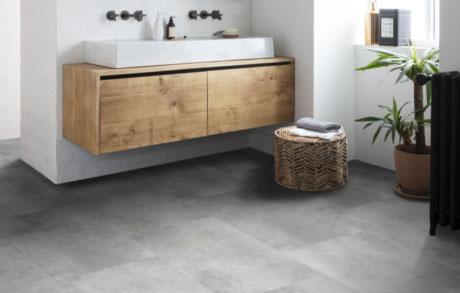 Vinylfliesen Cement Grey in warmgrauer Betonoptik verlegt in einem Badezimmer mit Holzwaschtischplatte und weißem großen Waschbecken