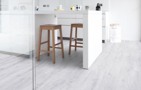 Vinylboden Chalk White in weißer Holzoptik verlegt in einer weißen Küche mit Theke und zwei Holzbarhockern