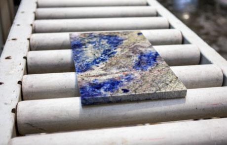 eine kleinere Lapislazuliplatte auf dem Förderband der Schneideanlage in der Werkshalle bei Dinger Stone