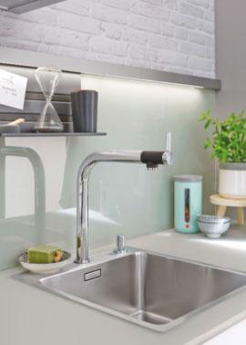 weiße Glasrückwand als Spritzschutz vor eingbauter Edelstahlspüle