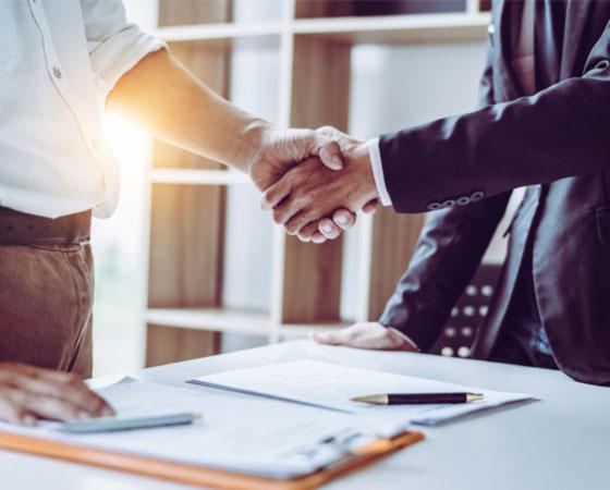 Nahaufnahme eines Händedrucks zweier stehender Geschäftspartner