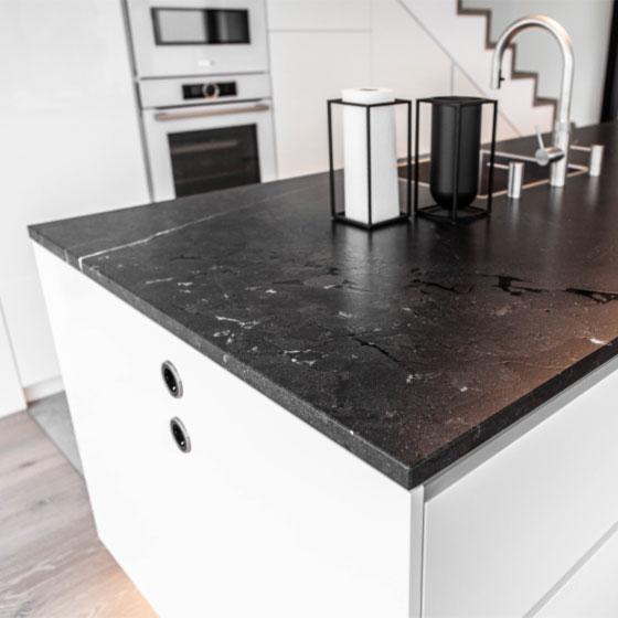 weiße Küche mit schwarzer Marmorarbeitsplatte