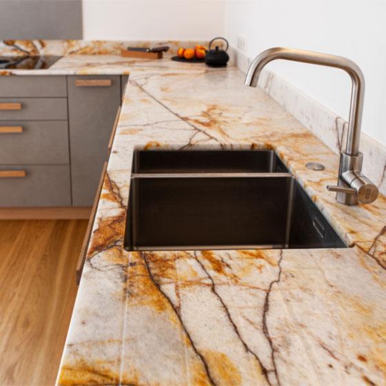 um die Ecke gehende Küchenarbeitsplatte aus Naturstein Samba Sunset mit Edelstahlunterbauspüle