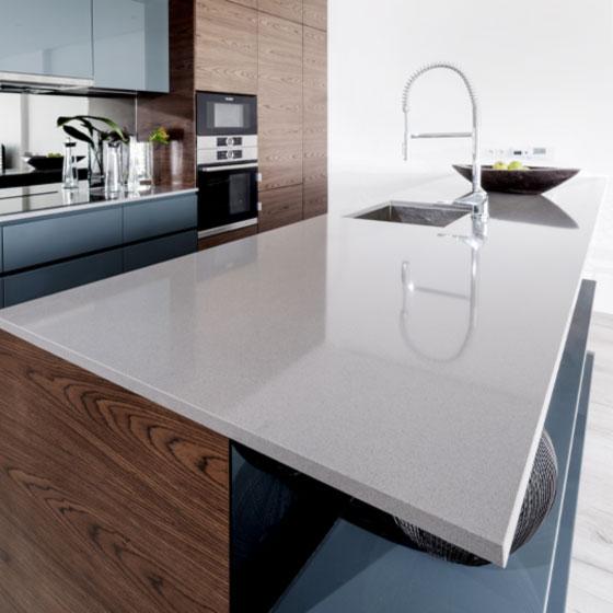 Küche mit heller Quarzsteinarbeitsplatte in Kombination mit Holzfronten