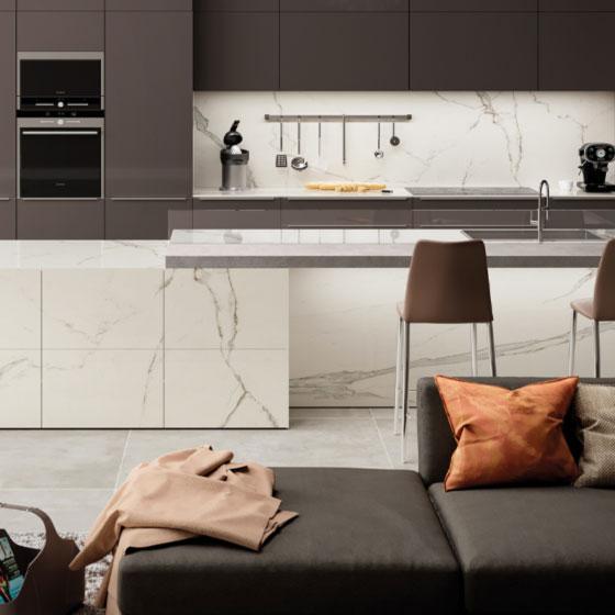 Küche mit hellbraunen Fronten und Thekenkombination aus Keramikplatten in weißer Marmoroptik