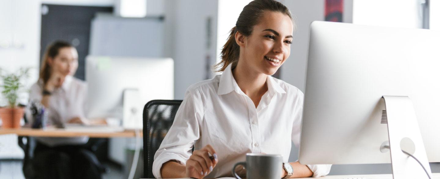 junge lächelnde Frau an ihrem Schreibtisch