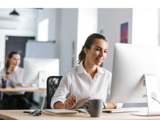 junge Frau im Innedienst an ihrem Arbeitsplatz mit Kaffeetasse und Computer