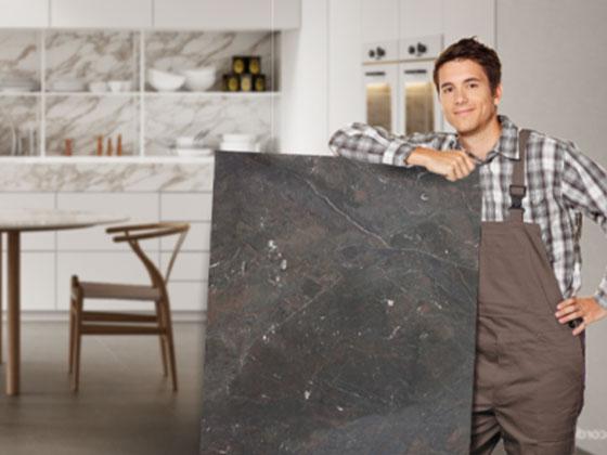 Monteur lehnt an einer Rohplatte im Hintergund eine Küche und ein Esstisch