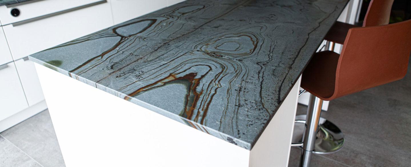 Thek eaus grauem Naturstein mit braunen Schlieren und Barhockern aus Leder und Stahlfüßen