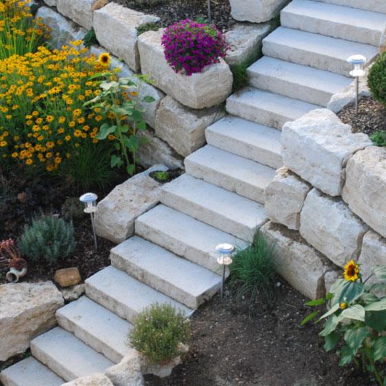 Natursteintreppe aus Kalkstein mit von Mauerstein gestützten Terrassen und üppiger Blumenbepflanzung