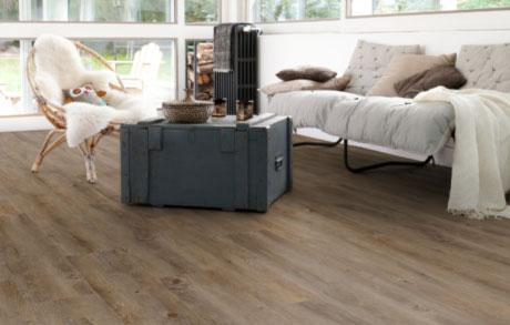 Vinylboden Oak Dark in dunkler Eichenholzoptik verlegt in einem Wohnzimmer mit Couch und bodentiefen Fenstern