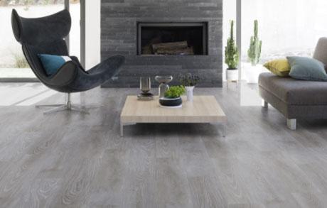 Vinylboden Oak Grey in grauer Eichenholzoptik verlegt in einem Wohnzimmer mit modernem Sessel vor einem offenen Kamin