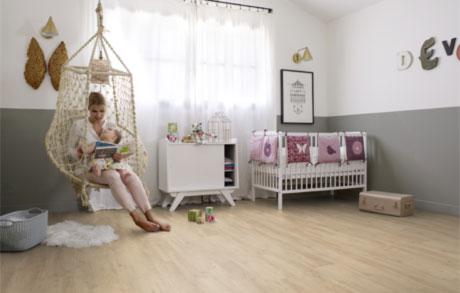 Vinylboden Oak Light in heller Eichenholzoptik verlegt in einem Kinderzimmer mit weißen Möbeln und Mutter, die ihrem Kind vorliest