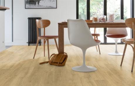 Vinylboden Oak Medium in mittelheller Eichenholzoptik verlegt in einem Esszimmer mit Holztisch und Tulipchairs