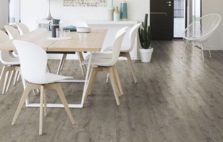 Vinylboden Old Wood in der Optik von gealtertem Eichenholz verlegt in einem Esszimmer mit weißen Schalenstühlen