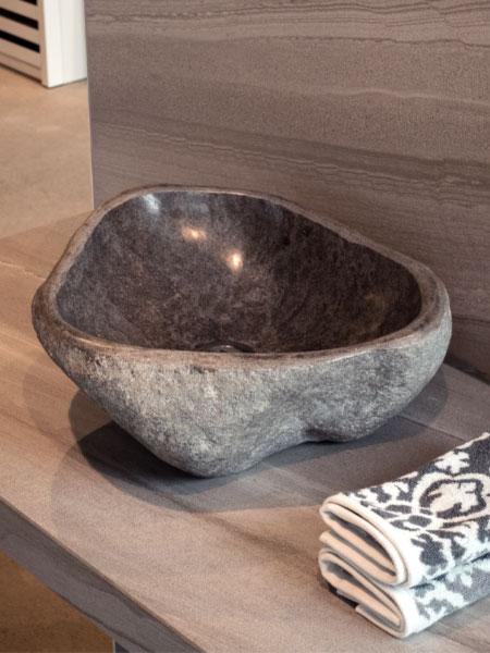 ausgehöhlter Flussstein als Waschbecken auf einer Holzplatte